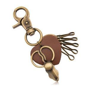 Patinovaný přívěsek na klíče, mosazný odstín, nůžky a hnědé srdíčko obraz